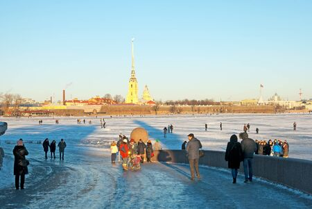 saints peter and paul: SAINT-PETERSBURG, RUSSIA, JANUARY 21, 2017: People walk on the Neva River ice and on The Old Saint Petersburg Stock Exchange and Rostral Columns. On the background is Saints Peter and Paul Fortress Editorial