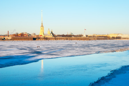 saints peter and paul: SAINT-PETERSBURG, RUSSIA, JANUARY 21, 2017: People walk on the Neva River ice. On the background is Saints Peter and Paul Fortress Editorial