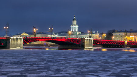 SAINT-PETERSBURG, RUSSIA, FEBRUARY 2, 2017: Night red illumination on The Palace Bridge over The Neva River in honor of the Chinese New Year. On the background is Kunstkamera Museum Editorial