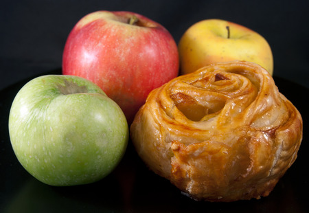 Bun with apple stuffing and green, red and yellow apples Stock Photo