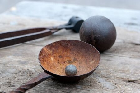 Old bullet for ancient gun and cannon ball on the wooden table