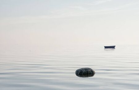 Empty boat on The Gulf of Finland (The Baltic Sea) and foggy horizon on the background. Saint-Petersburg. Russia