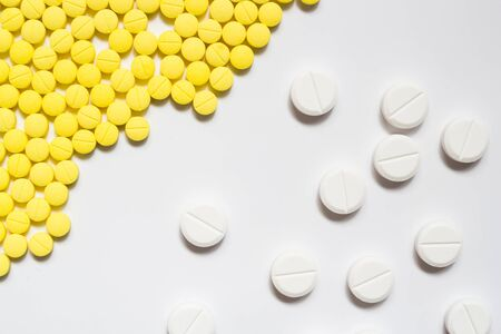 Yellow and white pills on white background with shadow photo