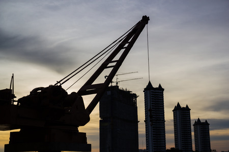 workingman: Crane on Building in Bangkok at sunset .