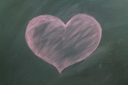 Red heart in chalk on a blackboard photo