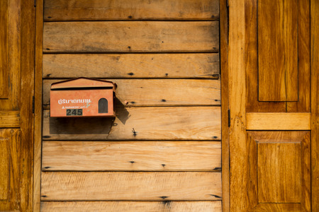 Red mailbox on wooden wall photo