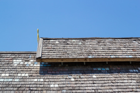 Wood roofing pattern detail on blue sky
