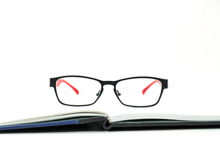 Glasses on a book on white background photo