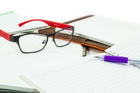 Glasses on books with a pen on white  photo