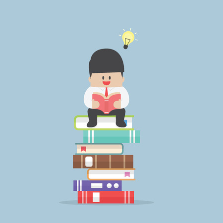 Businessman sitting on the stack of book and read it Stok Fotoğraf - 40618683
