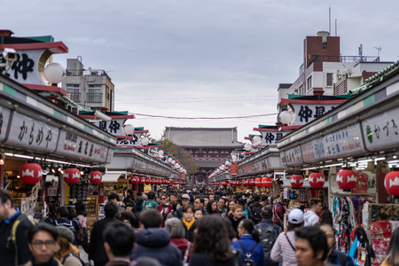 TOKYO, JAPAN - November 19, 2018:  Tourists at Nakamise shopping street connect to Sensoji Temple in Asakusa. Most popular attraction and oldest Temple in Tokyo.