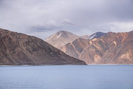 Pangong Lake with rocky mountains situated on the border with India and China in Ladakh region, State of Jammu and Kashmir, India.