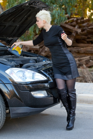 Lady is adding oil to the Car Engine photo