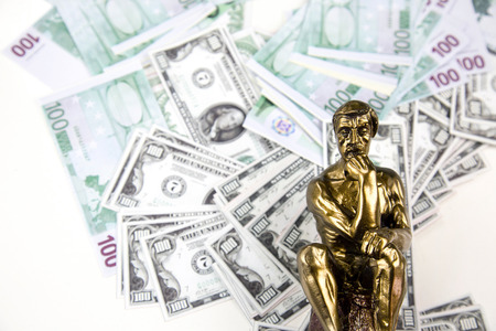 Money and Thinking Man Statue Stock Photo