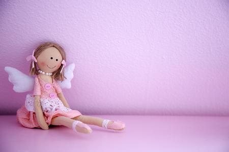 핑크 벽에 아기 인형
