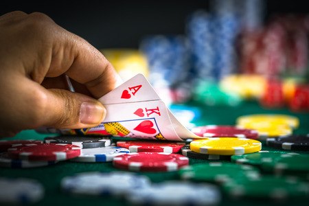 Gambling Hand Holding Best Game Card Series and Money Chips