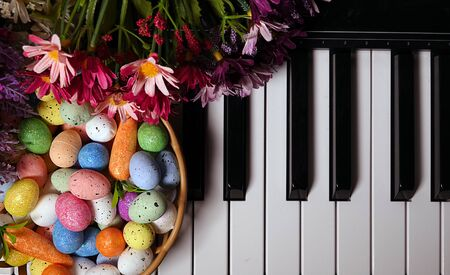 Colorful Paschal Easter Eggs and Piano Keys and Flowers