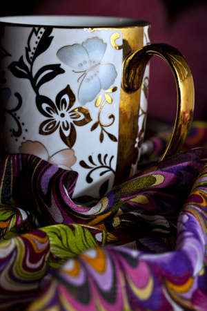 Decorative Coffee Cup on Colorful Fabric Photo