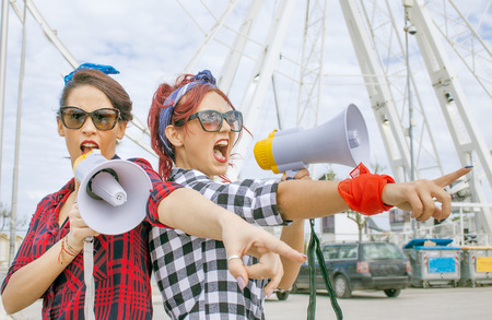 female protesters rally shouting political slogans with megaphone loudspeakers wearing red