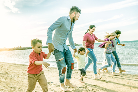 active family with many kids and friends on beach running together on the seashore. happy families of friends gettogether in summer beach holiday concept. Stock Photo