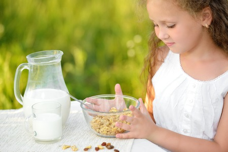 Close up portrait of little girl sitting near the table and having breakfast and drinking milk. Curly cute child sitting outdoor summer garden
