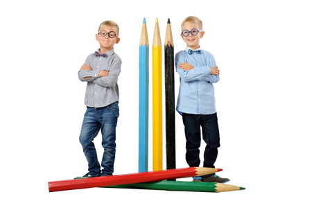 Full length portrait funny young boys in glasses and bowtie posing near huge colorful pencils. Educational concept. Isolated over white. School preschool