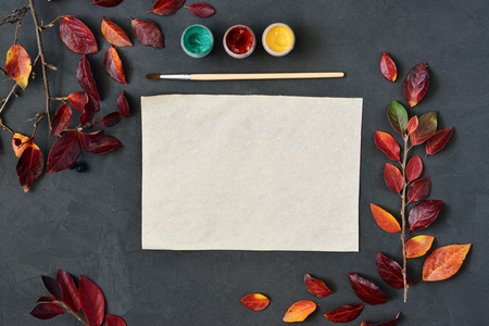 flat brushes: Autumn composition with craft paper, watercolors and brushes on chalk board, decorated with red leaves. Flat lay, top view, view from above