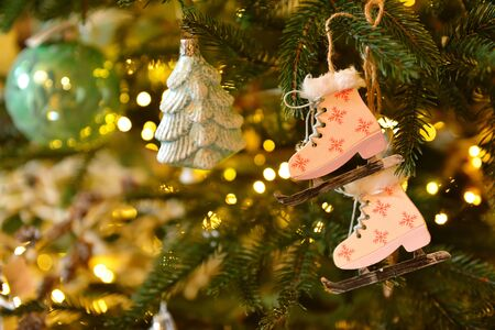fur tree: Christmas and New Year background with Eve Tree and decorations. Wooden handmade skates as toy for holiday fur tree. Stock Photo