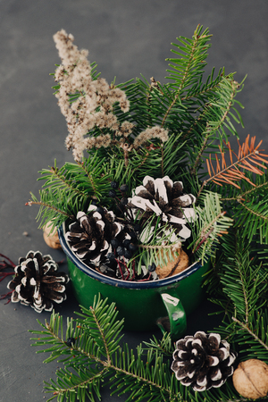 pinecones: Winter composition from spruce branches, pinecone, nuts in vintage mug on dark background
