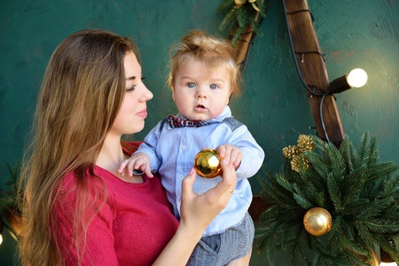 festively: Happy family mother and baby little son playing home on Christmas holidays. New Years holidays. Toddler with mom in the festively decorated room. Portrait of mother and baby boy