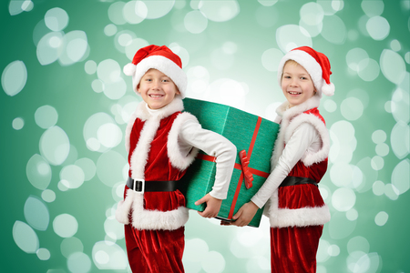 Adorable happy boys in santa clothes holding Christmas gift box. Isolated on green background with lights. Holidays, new year, x-mas concept. Stock Photo