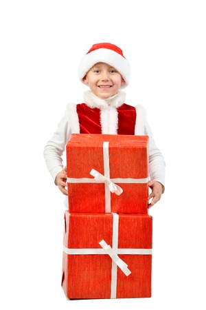 Adorable boy in santa clothes peeks out behind Christmas big gift boxs. Holidays, new year, x-mas concept. Full length portrait