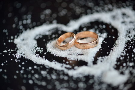 Wedding gold rings in sugar heart on dark wooden background. Valentines day, engagement event, love
