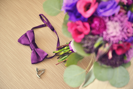 Beautiful Wedding purple Bouquet with brooch and groom bowtie cufflinks on beige chair. Background, floristic composition Stock Photo