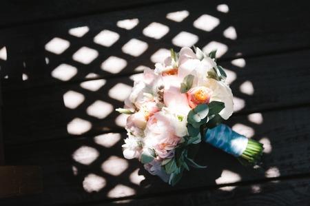 Bouquet de mariée de pivoines roses et ruban de menthe sur fond sombre avec des ombres difficiles. Composition floristique de mariage