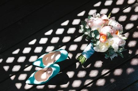 Bridal bouquet de pivoines roses et du ruban adhésif à la menthe, talons hauts chaussures sur fond sombre avec des ombres dures. Mariage composition floristique