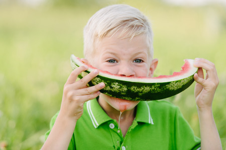 Cute little toddler boy with blond hairs eating watermelon in summergarden. Kid tasting healthy snack. Healthy food for children.