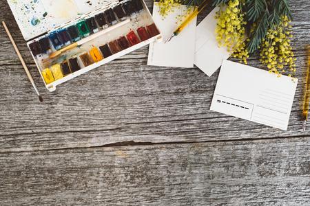 Area di lavoro. Cornice di corona con mimose, acquerelli, pennello e cartolina d'epoca su sfondo di legno. Archivio Fotografico