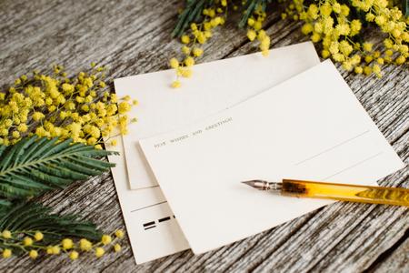 Cartoline postali d'epoca simulano con fiori gialli mimosas e inchiostro penna d'epoca su sfondo grigio di legno Archivio Fotografico