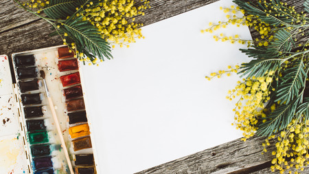 Area di lavoro. Cornice di corona con mimose, acquerelli, pennello e cartolina d'epoca su sfondo di legno.