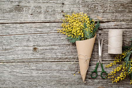 Make bouquet of mimosa. bandages twine and scissors on rustic wooden table Stock Photo