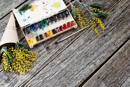 Area di lavoro. Cornice di corona con mimose, acquerelli, pennello su fondo in legno.