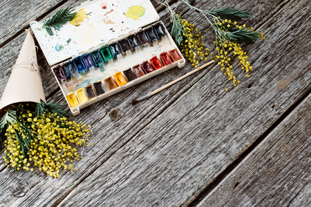 mimose: Workspace. Wreath frame with mimosas, watercolors, paintbrush on wooden background.