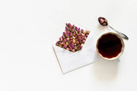 Purple dry roses in envelope and cup of tea on white background, flat lay, overhead view, Stock Photo