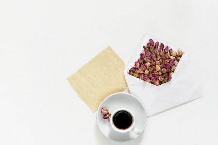 Purple dry roses in envelope and cup of tea with empty card for text on white background, flat lay, overhead view, Stock Photo