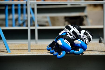 Patines en línea del rodillo en el parque del patín en fondo urbano gris