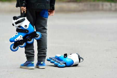 Poco hermoso chico con patines en sus manos Foto de archivo - 80031186