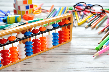 Close up view of abacus scores mental arithmetic with colorful back to school supplies over white table. Space for text. Flat lay style