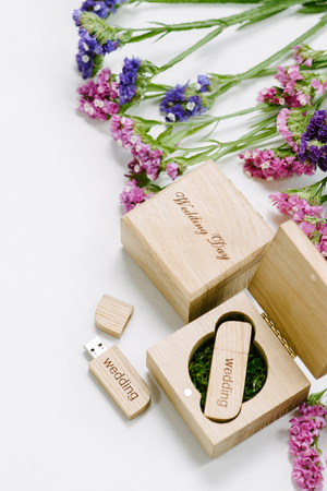 Original gift present. Beautiful white wedding Usb flash drive in Vintage Handmade wooden box with wildflowers . Stock Photo