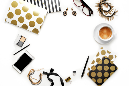 Flat lay fashion feminine home office workspace with phone, cup of coffee, stylish black gold notebooks, cosmetics and jewelry on white background. Women's business work desk form above with space for text
